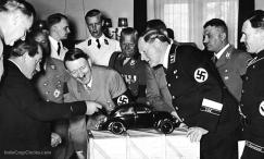 Adolf Hitler (1889 - 1945), the German Dictator admires a model of the Volkswagen car and is amused to find the engine in the boot. He is with the designer Ferdinand Porsche (left), and to the right Korpsfuhrer Huehnlein, Dr Ley, Schmeer, and Werlin. (Photo by Hoffmann/Getty Images)