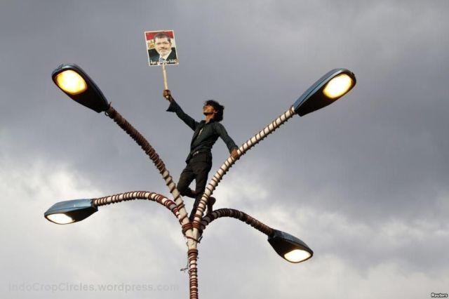 pendukung Mursi memegang foto di atas lampu jalanan dlm demonstrasi di Sana'a, Yaman, utk menunjukkan solidaritas