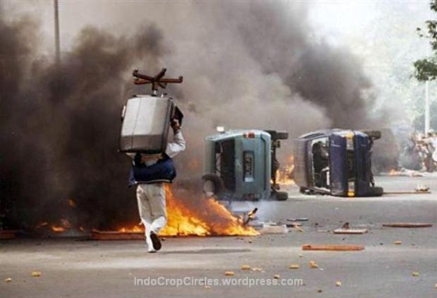 Seorang penjarah dengan kursi jarahan melewati mobil-mobil yang terbakar pada kerusuhan tanggal 14 Mei 1998 di Jalan Hasyim Ashari, Jakarta. (Bodhi Chandra)