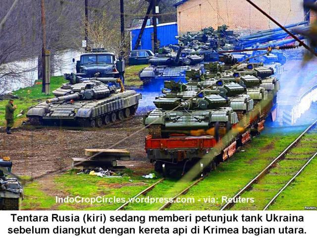 tentara Rusia (kiri) memberi petunjuk tank Ukraina sebelum diangkut dengan kereta api di Krimea utara