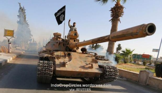 Militan ISIS di atas tank dalam parade militer di sepanjang jalan provinsi Raqqa utara, 30 Juni 2014. (REUTERS)