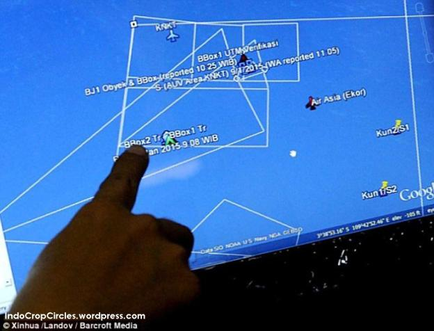 A member of Indonesian Research and Technology Application Agency points at the coordinates where signals of AirAsia flight QZ8501 black box were detected on Sat