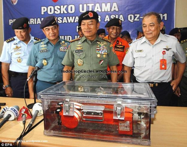 Indonesian army and naval personnel look at the flight data recorder that was in the first black box.(EPA).