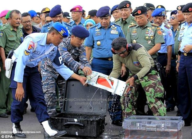 Indonesian officers take the plane's flight data recorder and move it into a large plastic container. (EPA).