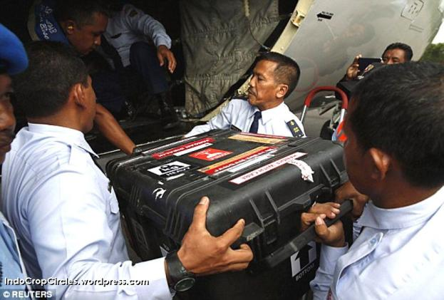 The AirAsia aircraft's flight data recorder in its black box is unloaded by Indonesian Air Force flight crew (AP).