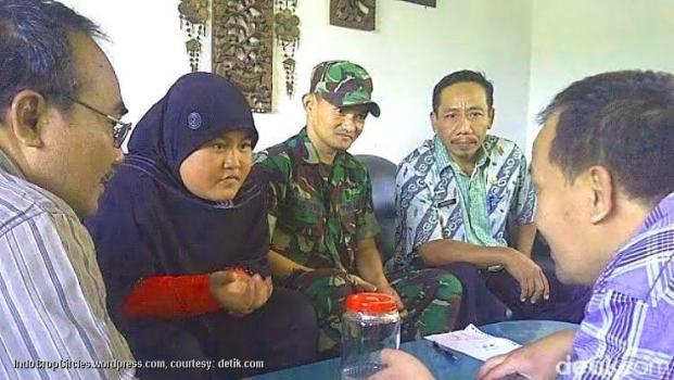 Pipit (berkerudung), didampingi petugas koramil dan pejabat setempat (courtesy: detik.com/Enggran EB)