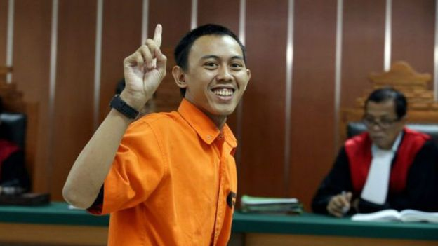 Dodi Suridi tertawa dan mengangkat jari telunduk ketika berada di PN Jakarta Barat (pict: EPA)