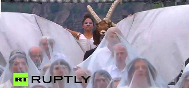 Sosok manusia kambing Baphonet membuat pintu masuk, didahului oleh orang-orang yang mengenakan cadar putih seperti pengantin sebelum pernikahan. (pict: RT)